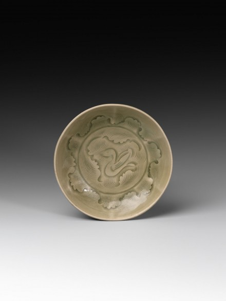 A CARVED YAOZHOU CELADON 'DUCK IN WAVES' SHALLOW BOWL