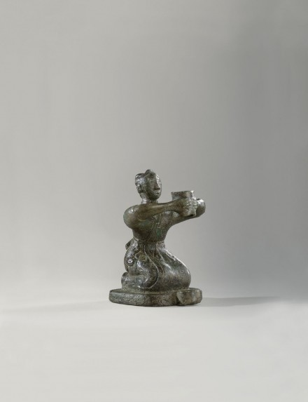 AN ARCHAIC BRONZE KNEELING FIGURE