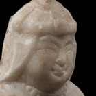 A SMALL WHITE MARBLE SEATED FIGURE OF A 'FOREIGNER' WITH LION CUB