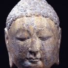A GRAY LIMESTONE HEAD OF THE BUDDHA