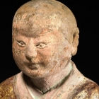 A PAINTED AND GILDED STONE FIGURE OF A LUOHAN