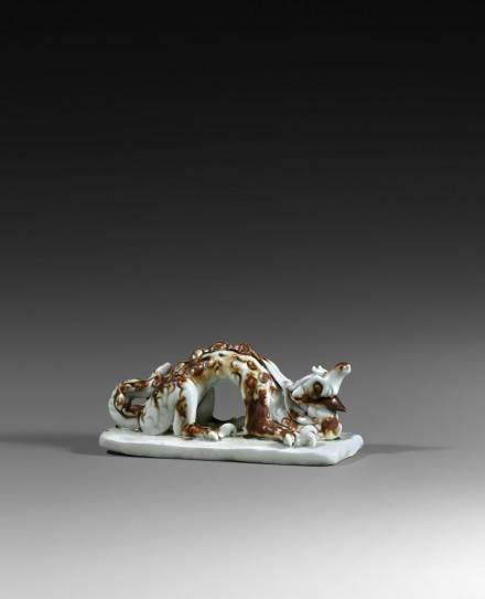A QINGBAI GLAZED IRON-BROWN SPLASHED PORCELAIN DRAGON-FORM BRUSHREST