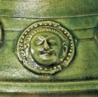 A GREEN-GLAZED POTTERY COVERED VASE WITH APPLIED MEDALLIONS