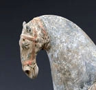 A PAINTED POTTERY FIGURE OF A SADDLED HORSE