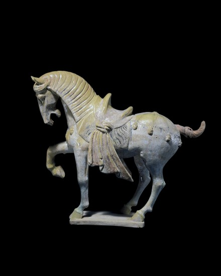A GLAZED AND PAINTED POTTERY FIGURE OF A PRANCING HORSE