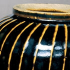 A WHITE-RIBBED BLACK-GLAZED GLOBULAR JAR