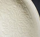 A LARGE MOULDED DINGYAO WHITE PORCELAIN 'BOYS AND PEONIES' BOWL