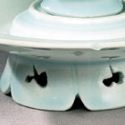 A YINGQING GLAZED PORCELAIN FLOWER-SHAPED WINECUP AND STAND