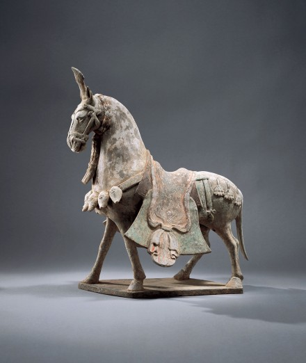A PAINTED POTTERY CAPARISONED STRIDING HORSE