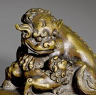 A BRONZE WEIGHT SURMOUNTED BY A BUDDHIST LION AND CUB
