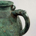 A BRONZE TRIPOD POURING VESSEL (HE)