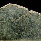 AN INCISED GREEN JADE PLAQUE