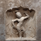A LIMESTONE BLOCK WITH DANCER IN A NICHE