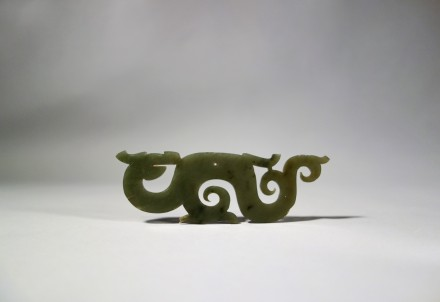 A GREEN JADE OPENWORK DRAGON-FORM PENDANT (HUANG)