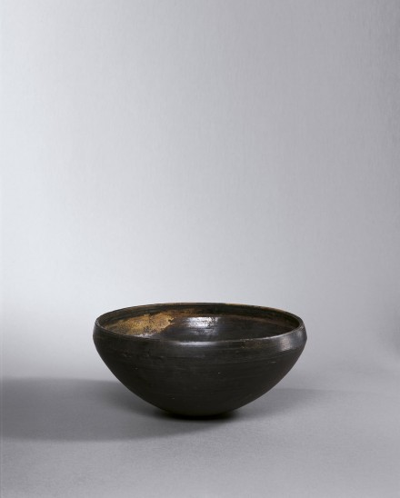 A BURNISHED BLACK POTTERY ALMS BOWL (PATRA)