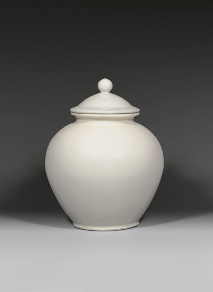 A GLAZED WHITE STONEWARE JAR AND COVER