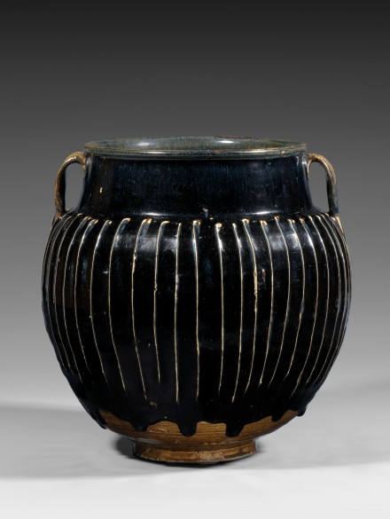A LARGE BLACK-GLAZED WHITE-RIBBED STONEWARE JAR