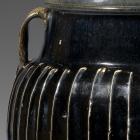 A LARGE BLACK-GLAZED WHITE-RIBBED STONEWARE JAR