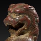 A SMALL RED SANDSTONE SEATED FIGURE OF A LION
