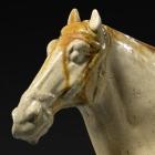 A GLAZED POTTERY FIGURE OF A SADDLED HORSE